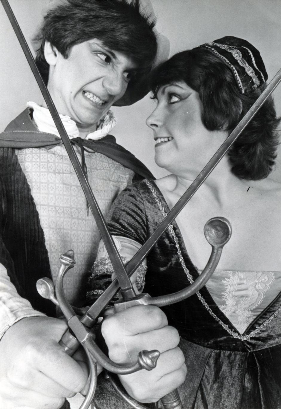 Image of actors crossing swards.