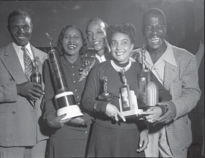 3 men and 2 women holding trophies