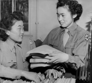 Two women filing papers
