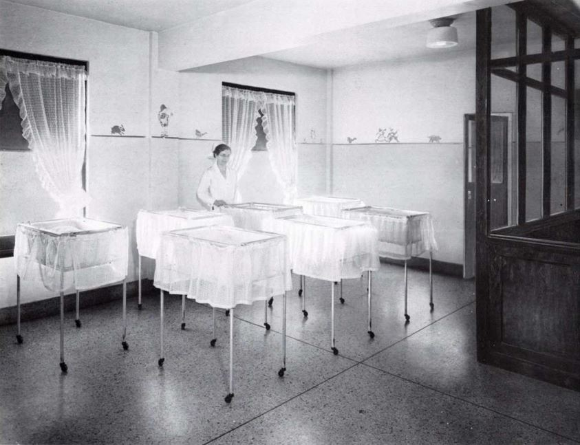 woman standing next to two cribs