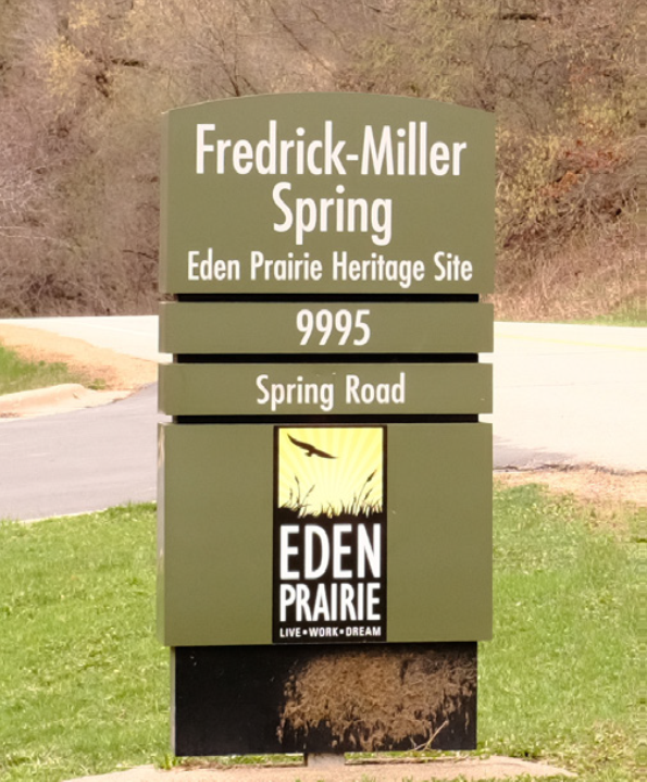 Green sign with text that reads: Fredrick-Miller Spring Eden Prairie Heritage Site 995 Spring Road
