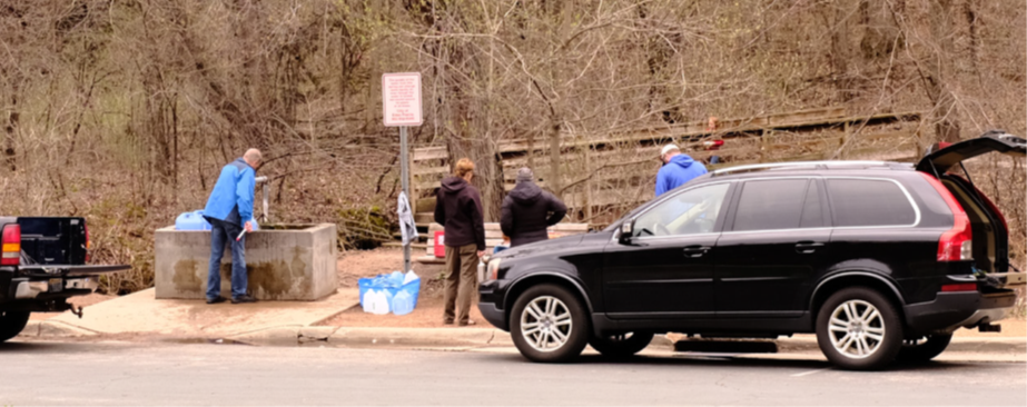 Black car with open trunk as 4 people stand looking at ground